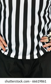An Ice Hockey Referee is standing with his arms on his chest