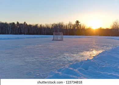 Ice hockey rink on frozen lake at sunset