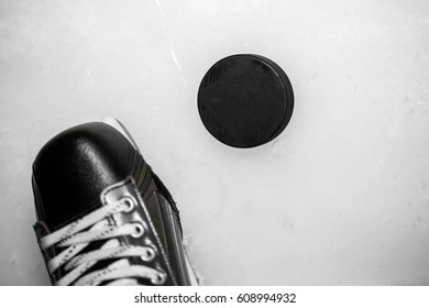 Ice hockey shoe and puck on rink scratches surface for texture or background, winter closeup top view image