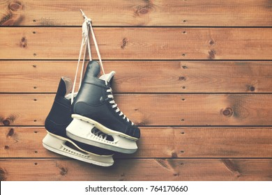 ice hockey skates hanging on nail on wooden plank background