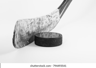Ice hockey stick blade wrapped in scuffed white tape and a used puck on a white background; black and white image