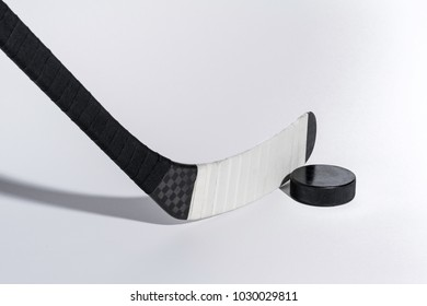 Ice hockey stick and puck on isolated white background, equipment for hockey player in winter game season, closeup on Wooden head ice hockey stick Kevlar design.