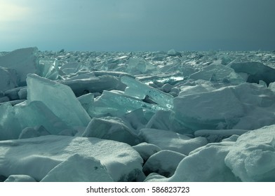 ice hummocks on the northern shore of Olkhon Island on Lake Baikal. Transparent blocks of crystal clear ice crawl ashore. Colorful refraction of rays of rising sun. Ice Storm. Photo partially tinted.
