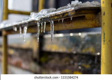 Ice and icicles on old rustic yellow stair steps outside slipping hazard risk