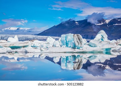 Ice lagoon in Iceland. Ocean Bay is surrounded by volcanic mountains and glaciers. Icebergs and ice floes are reflected in the mirrored water