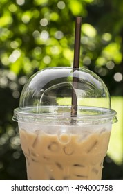 Ice latte coffee in plastic cup on garden background.Soft drink at a cafe in the park.