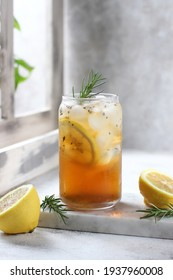 Ice lemon tea with rosemary leave. Isolated on the squre marble board. With lemon slice beside. Bright light with the window beside