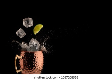 Ice and lime falling into copper mug for a Moscow Mule cocktail