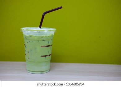 Ice milk green tea on wooden table, cold drink