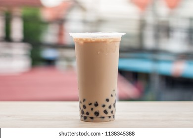 Ice milk tea with bubble in plastic glass put on the wood floor in the city, The popular drink in asia call ice milk tea with boba favorite in Thailand