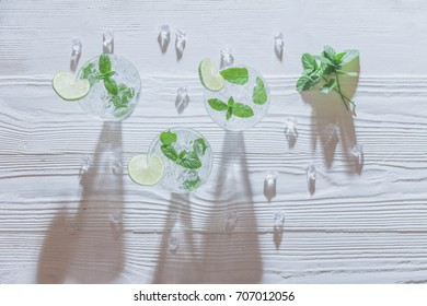 Ice mojito. Cocktail with lime and mint leavess on white old rustic wooden background. top view
