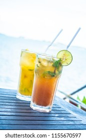 Ice mojito drinking glass with tropical sea ocean and beach view