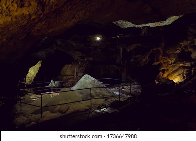 Ice mountain in a deep dark cave in the old mountain. Clear water froze among the dark walls of the rock in the dungeon. Natural refrigerator in nature. Landscape orientation