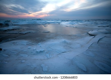 ice at the North Sea coast while a scenic sunset with vivid sky after several days of extremly low temperatures