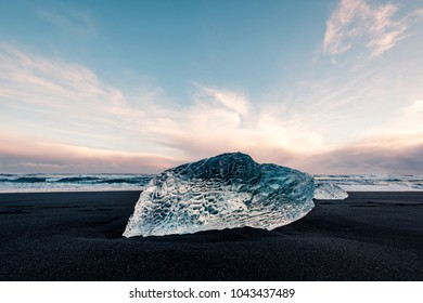 Ice on the black volcanic beach near Jokulsarlon glacier lagoon, winter Iceland. Detail of a glacial fragment of ice at black sand beach in beautiful evening light.