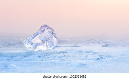 Ice on the frozen lake at sunset. Shallow depth of field. Beautiful winter background
