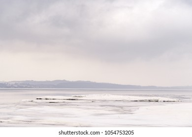 Ice on a frozen lake in the winter with dark clouds in the sky