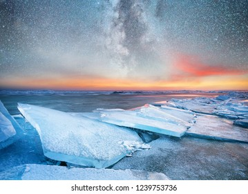 Ice on the ocean shore at the night time. Sea bay and stars at the night time. Milky way above ocean, Norway. Beautiful natural landscape in the Norway