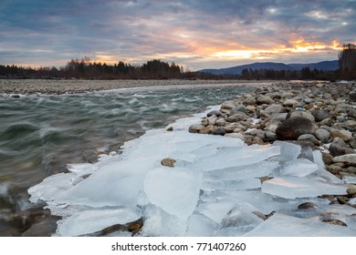 Ice on the shore of a mountain river at sunset.