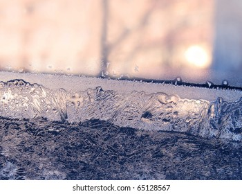 ice patterns and sunlight on winter window