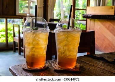 Ice peach tea in plastic cup on wooden table in coffee shop.