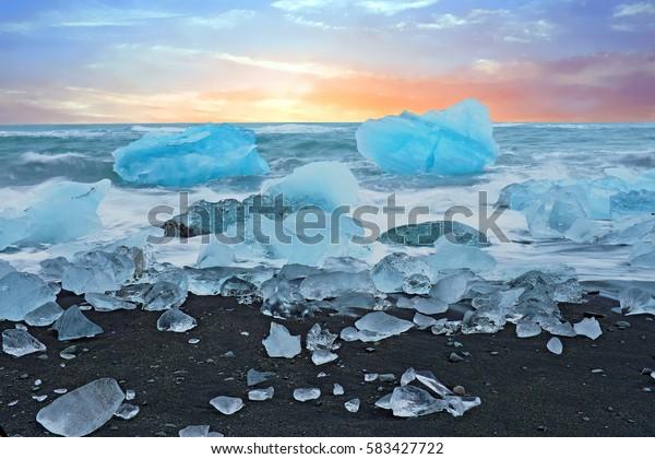 Ice rocks on a black sand beach at Jokulsarlon in Iceland at twilight