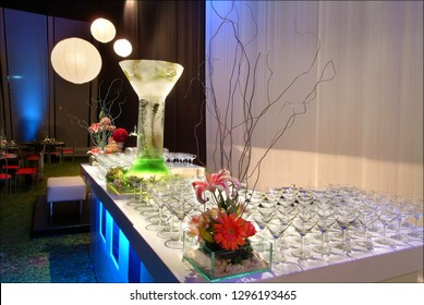 Ice sculpture drinks table with side floral arrangements and ambient setting.