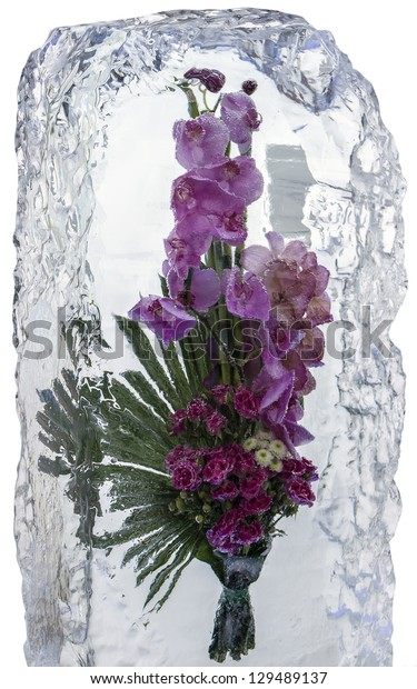 Ice sculpture. A lush bouquet of flowers frozen in a block of ice.