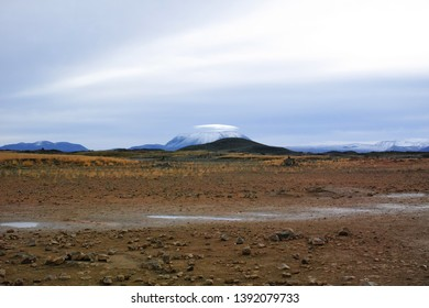 Ice sheet mountain covered by cloud in desolate field.