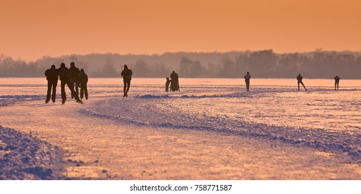 Ice Skaters on frozen lake seen on their back under orange sunset