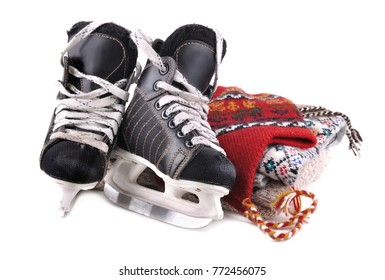 ice skates for child next to cap and pullover on white background