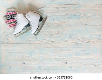 ice skates with mitten on wooden background with text space top view