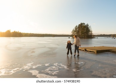 Ice skating on a frozen Lake in southern Sweden. Mother and her little daughter skating in the light of a sunny afternoon in winter.