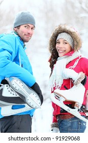 Ice skating winter couple smiling happy holding ice skates outdoors. Beautiful young couple, Asian woman, Caucasian man outside on snow winter day.