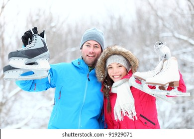 Ice skating winter couple smiling happy and excited showing ice skates outdoors in snow. Beautiful young multi-racial couple healthy lifestyle concept.