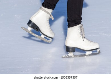 Ice skating, woman legs wearing white leather skates, training on a frosen snowy skating rink in winter close up.