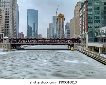 Ice and snow cover the surface of the Chicago River during a frigid January evening