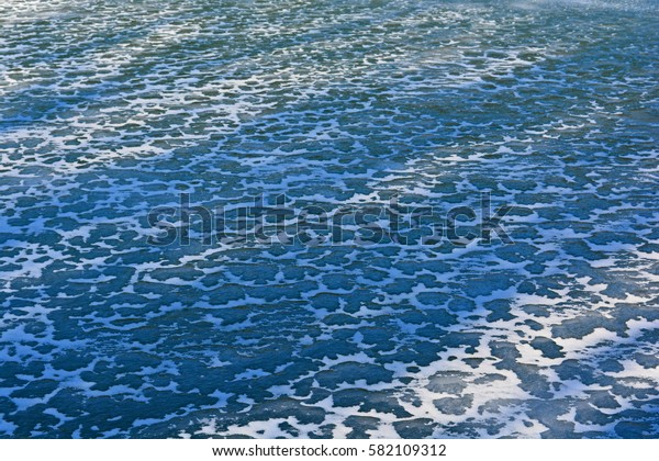 Ice with snow on a frozen lake. Can be used as background or texture