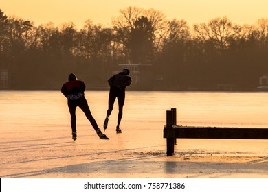 Ice speed skating silhouettes in orange evening light of setting sun on frozen lake in the Netherlands