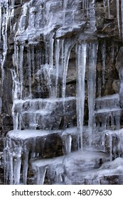 Ice and stone: a frozen waterfall on the rocks.
