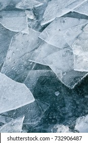 Ice surface with floes in close up; Winter time; Broken and refrozen ice surface; Ice fragments on water surface in top view - upright format