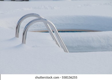 Ice swimming pool in the winter, Steps, hand-rails and garden chair in the frozen blue pool ice-hole