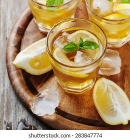 Ice tea with lemon and mint, selective focus and square image