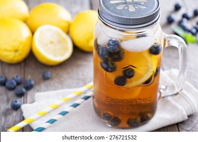 Ice tea in mason jar mug with lemon and blueberries refreshing in hot summer day