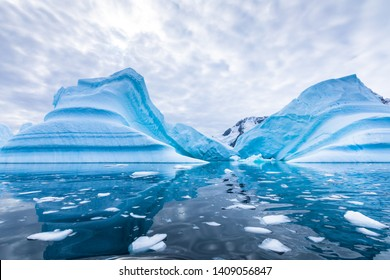 Iceberg in Antarctica floating in the sea, frozen landscape with massive pieces of ice reflecting on water surface, Antarctic Peninsula