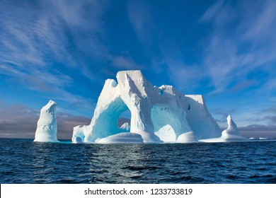 An Iceberg Of Colossal Size In The Form Of A Castle With Arches And Columns Floats In The Cold Waters Of Antarctica – Stock Image