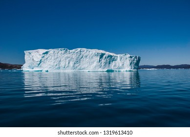 Iceberg in fjord, Greenland. Iceberg floating in the fjord water. Blue sky.