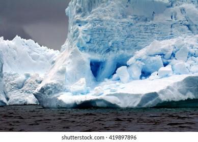 Iceberg floating in the frigid waters of Antarctica under stormy skies