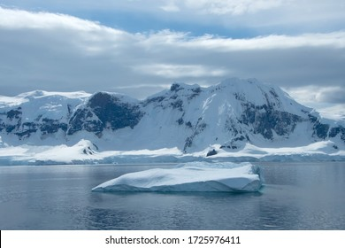 An iceberg floating in front of a snow covered Elephant Island, Antarctica.