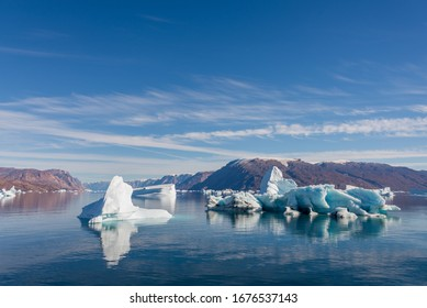 Iceberg in Greenland fjord with reflection in calm water. Sunny weather. Golden hour.